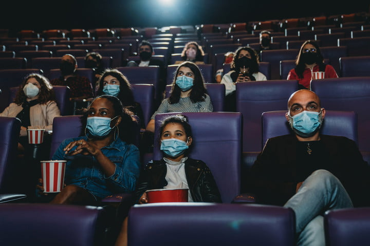 People at the movie theater watching a movie. They are wearing protective face masks. Focus on a family with one child.