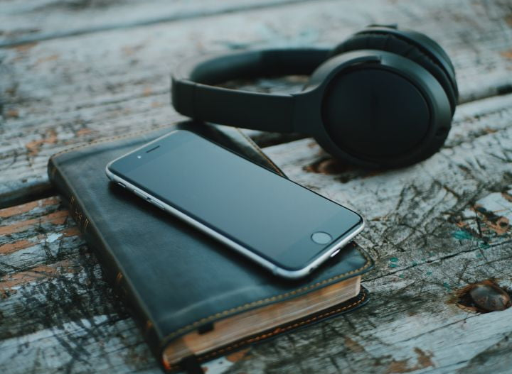 podcasts to listen during black history month and beyond phone with headphones aaron burden 01