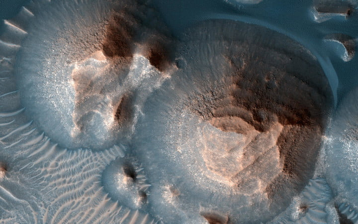 This image shows several craters in Arabia Terra that are filled with layered rock, often exposed in rounded mounds. The bright layers are roughly the same thickness, giving a stair-step appearance.