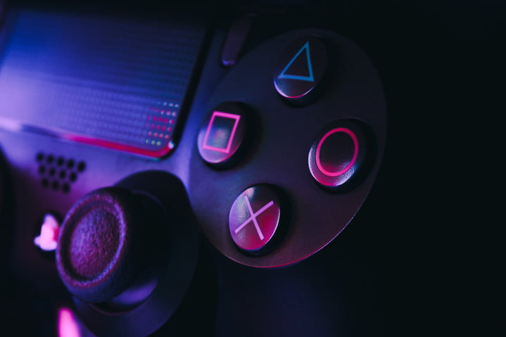 Playstation 4 gamepad on black background with colored lights