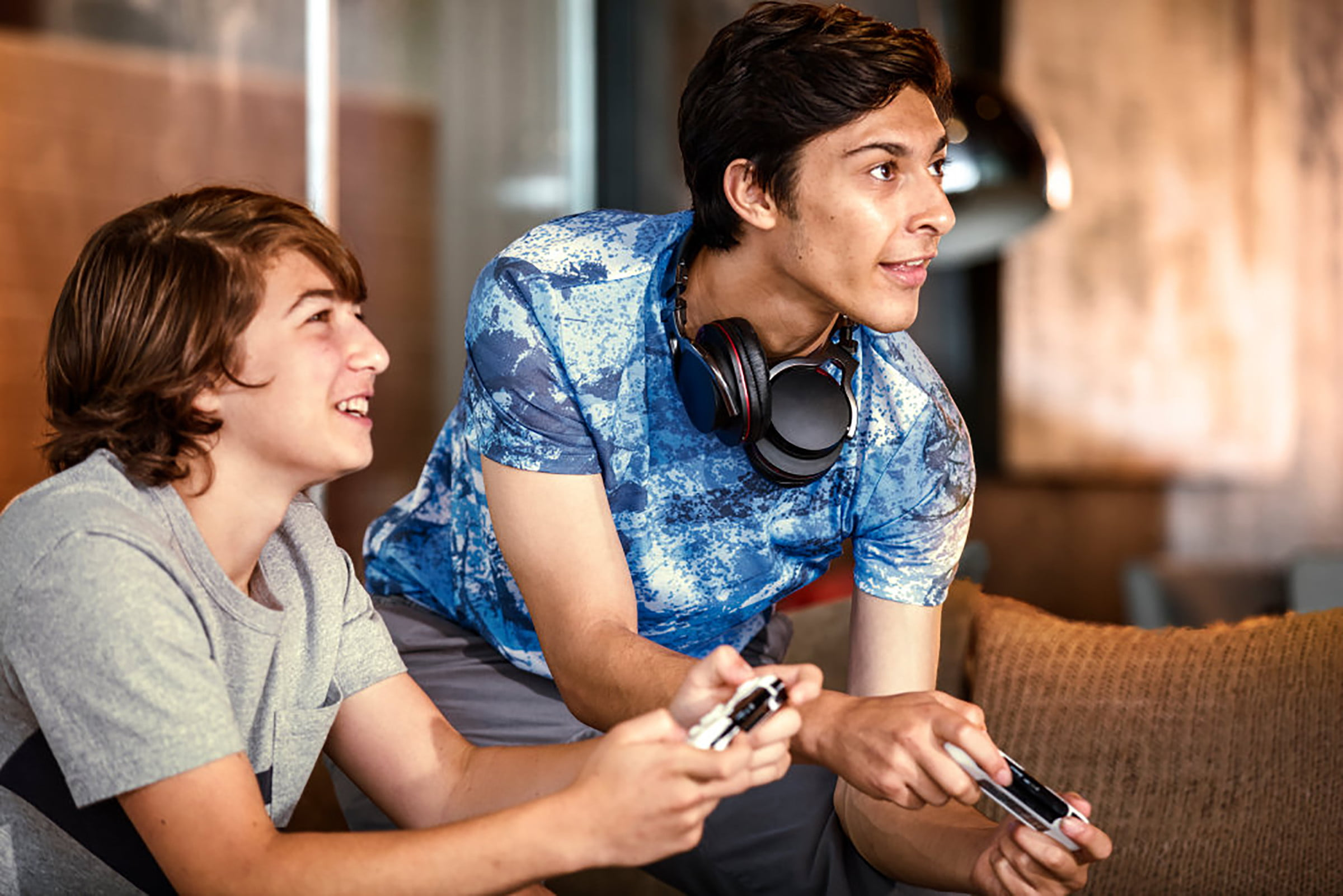 Teens with headphones playing video games.