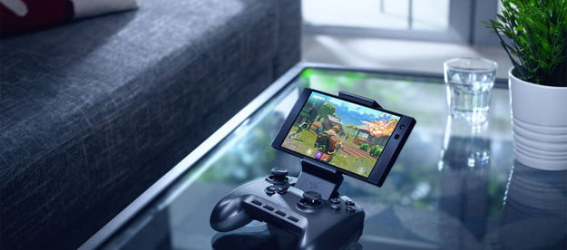 Razer Raiju Mobile Games Controller with a smartphone attached, on a table in a sitting room