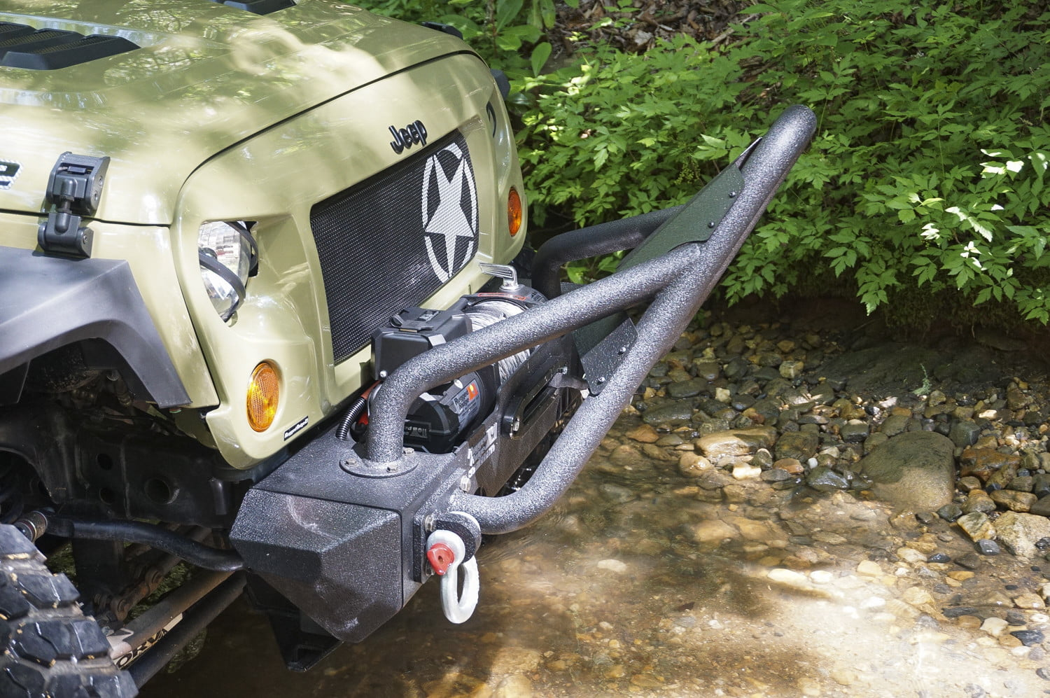 Front grill and winch of a Green Jeep Wrangler Unlimited