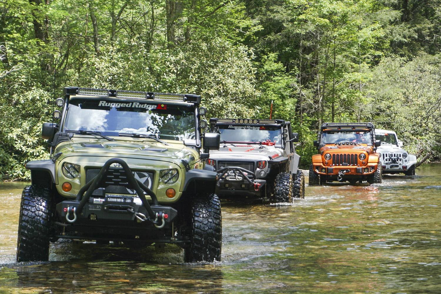 Four different colored Jeep Wrangler Unlimiteds driving up a riverbed