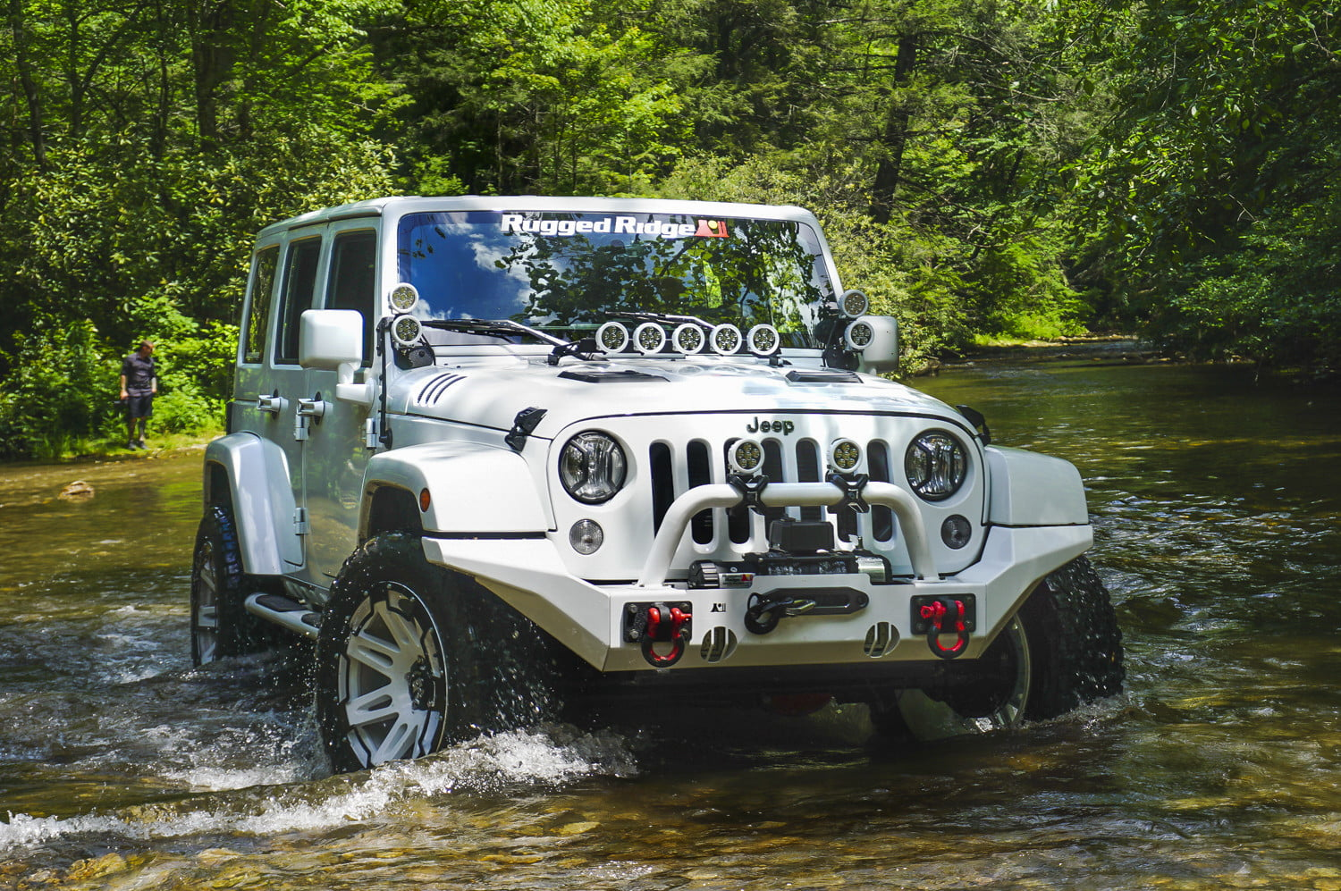 White Jeep Wrangler Unlimited driving through a creekbed