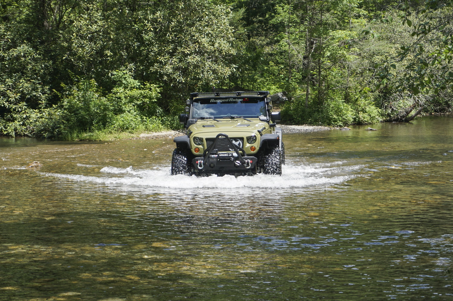 Green Jeep Wrangler Unlimited driving through a riverbed