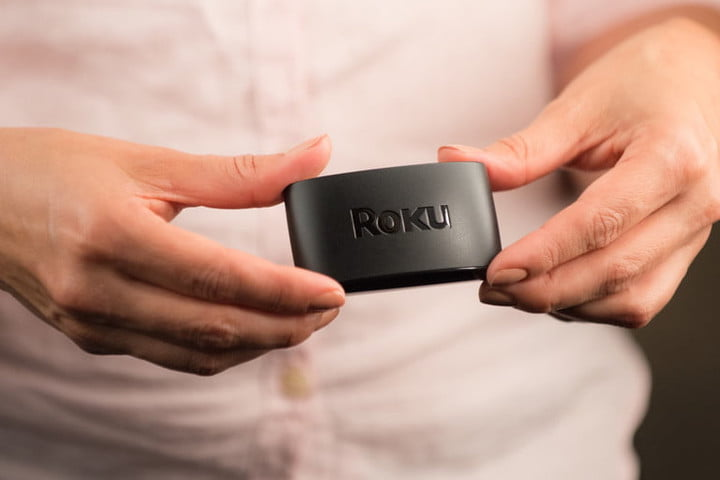 Roku Express in a person's hands.