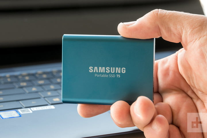 A hand holding the Samsung T5 in front of a laptop.