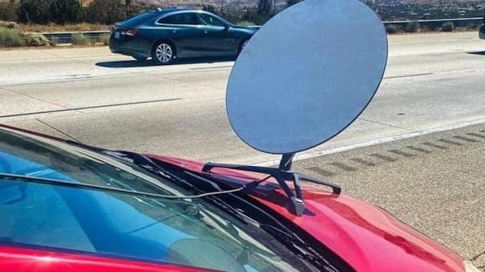 A satellite dish bolted to a car's hood.