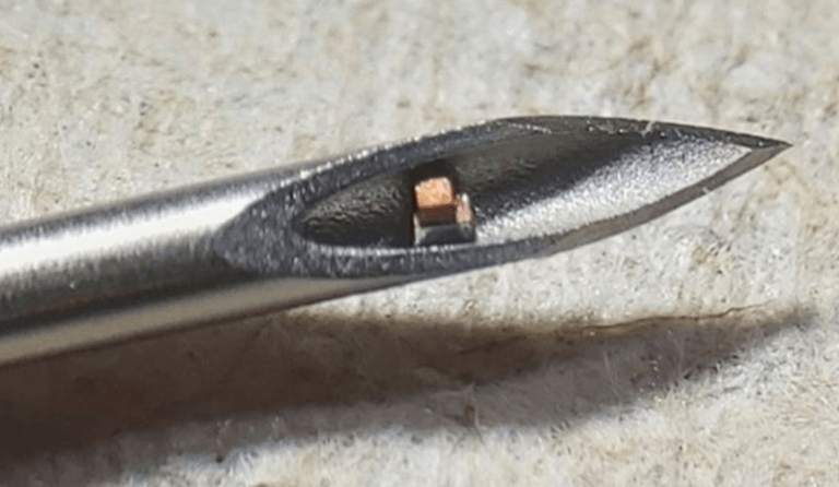 small health tracking chip shown inside the tip of a hypodermic needle