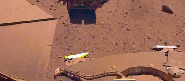 To clean a bit of dust from one of its solar panels, NASA's InSight lander trickled sand above the panel. The wind-borne sand grains then picked up some dust on the panel, enabling the lander to gain about 30 watt-hours of energy per sol on May 22, 2021, the 884th Martian day of the mission.