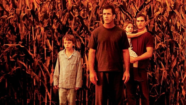 The Cast of Signs standing in a corn field.