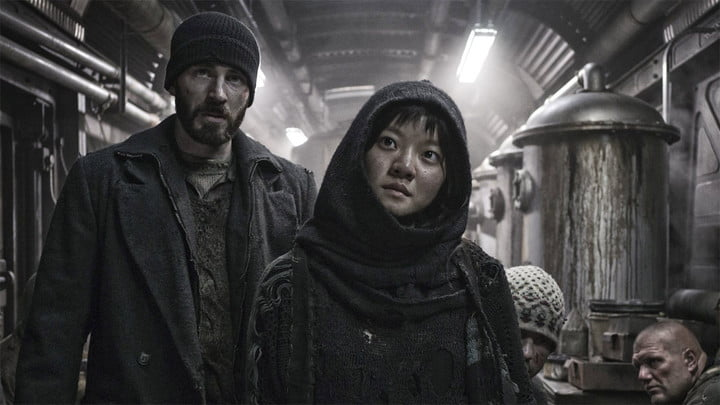 Chris Evans and another passenger in a dimly-lit train car in Snowpiercer.