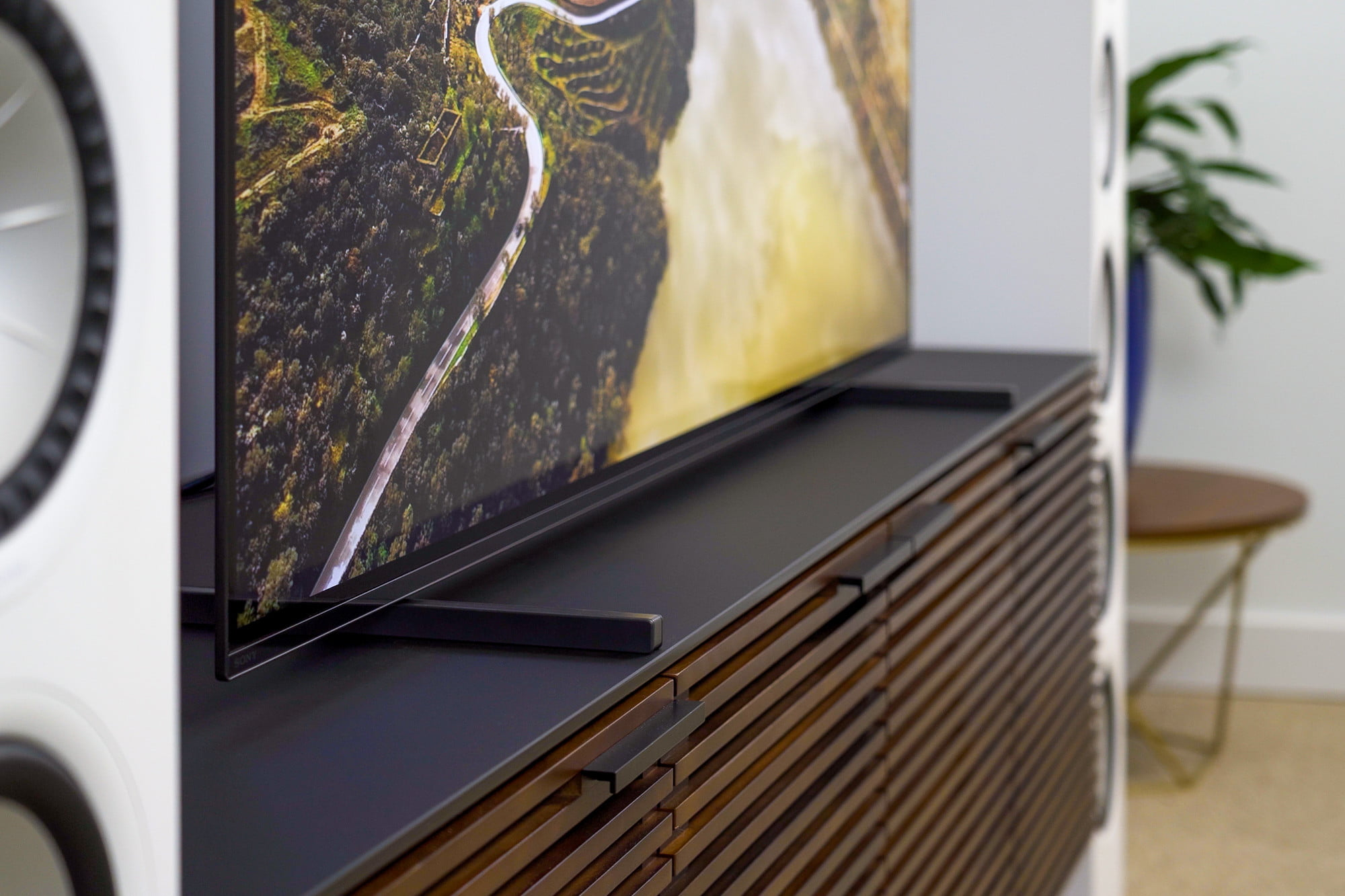 Sony A80J sitting on media console. Image is a closeup on the tv's stand.