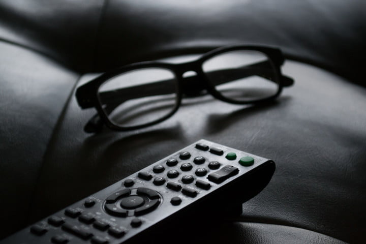A black-and-white photo of a remote control and glasses.