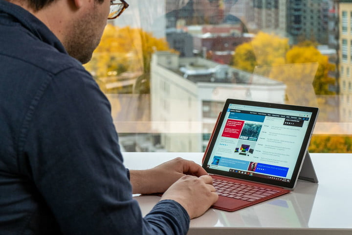 A person typing on a Surface Pro 7 with a red Type Cover.