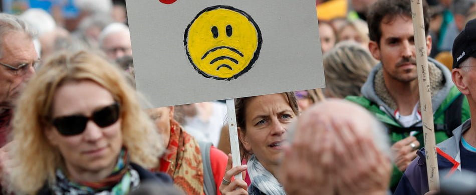 an anti-5G protestor holing a sign