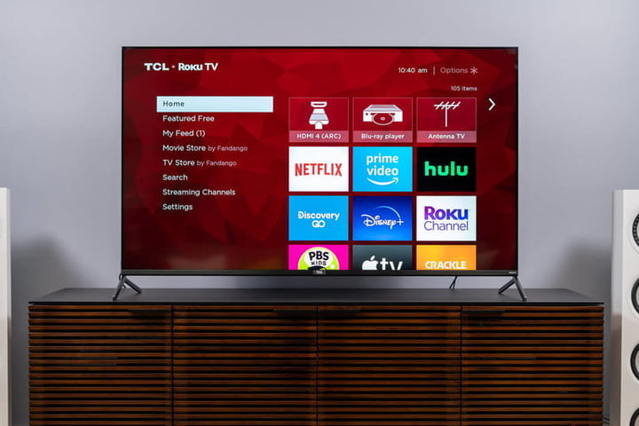 A smart TV on a wooden TV stand.