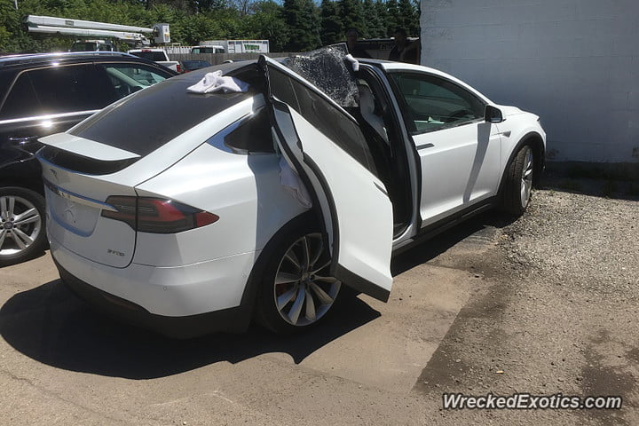 tesla model x falcon wing door ripped off with by garage 900x600