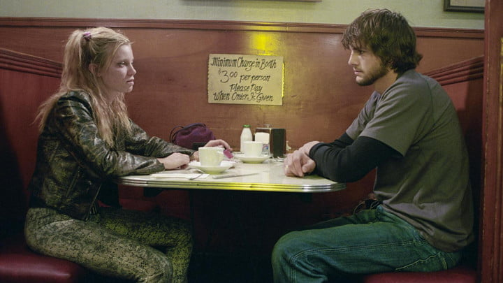Amy Smart and Ashton Kutcher sitting across from each other in a diner booth.