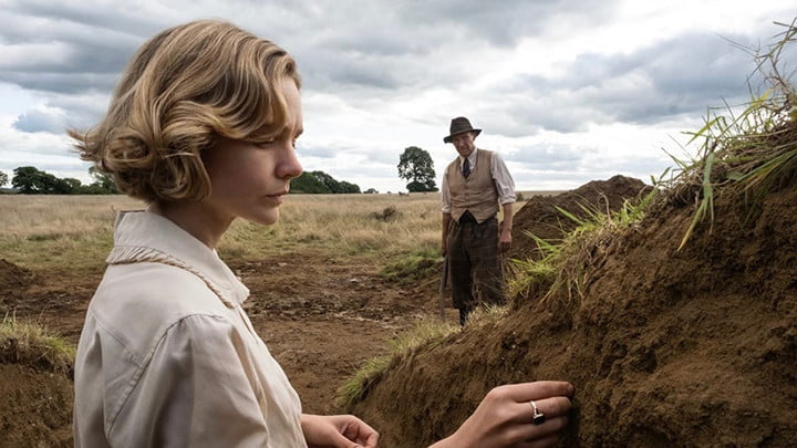 Carey Mulligan examines a pile of dirt in the film The Dig.