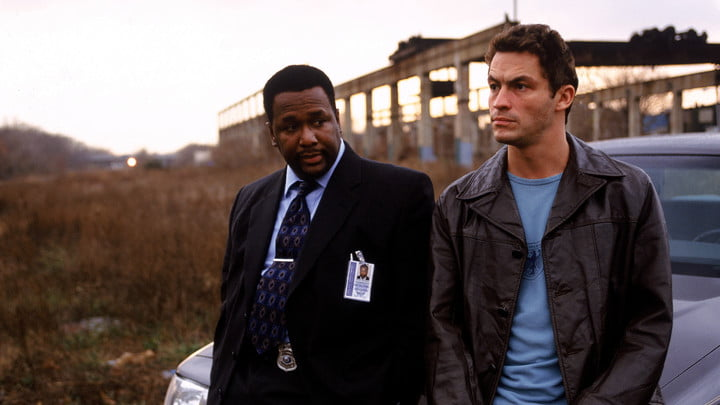 Two characters from The Wire leaning against a car.