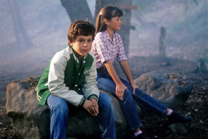 Kevin and Winnie sitting on a rock in a scene from The Wonder Years.