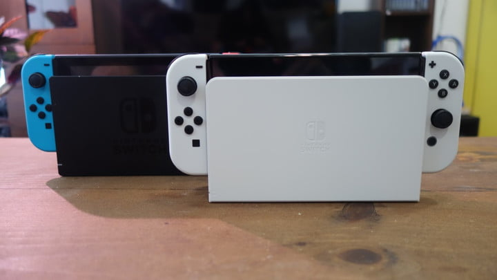 A Nintendo Switch OLED model in its dock next to a regular Switch dock.
