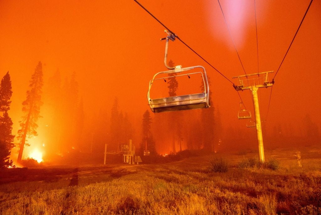Flames from the Caldor Fire surround a chair lift at Sierra-at-Tahoe Resort.