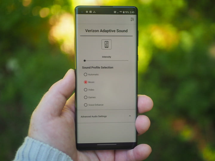 Hand holding an Android smartphone showing the Verizon Adaptive Sound menu.