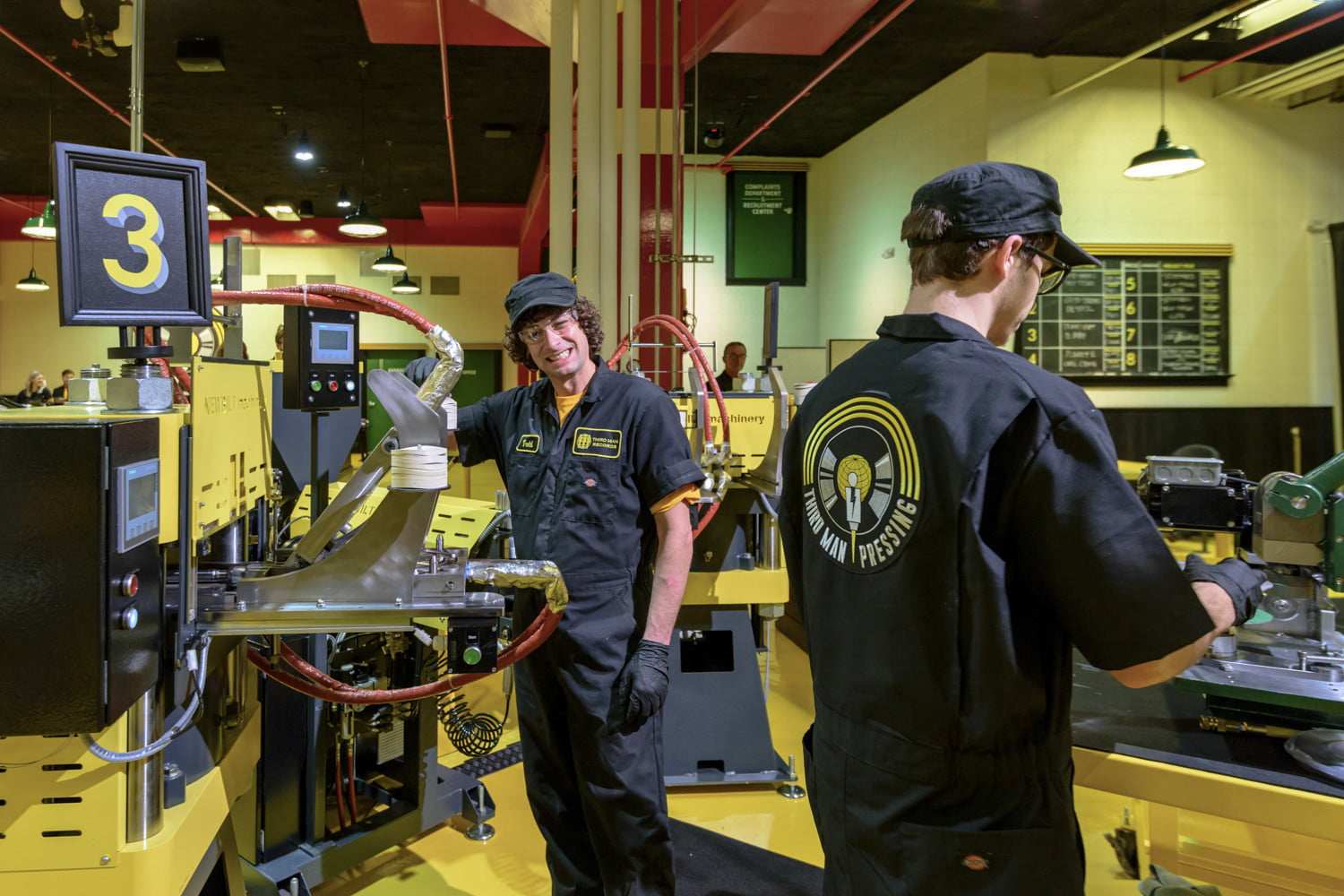 man-looking-at-camera-while-making-vinyl-record-in-machinery