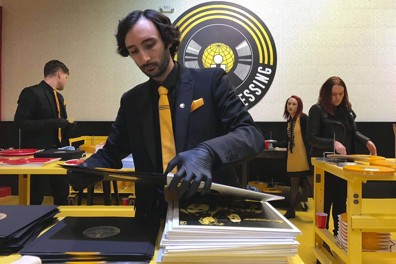 man-placing-records-into-covers-and-stacking-them_1