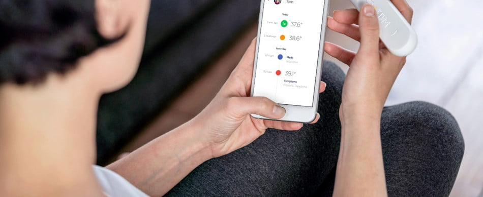 Withings - Thermo Smart Temporal Thermometer being compared with the digital display by a person, over the shoulder view.
