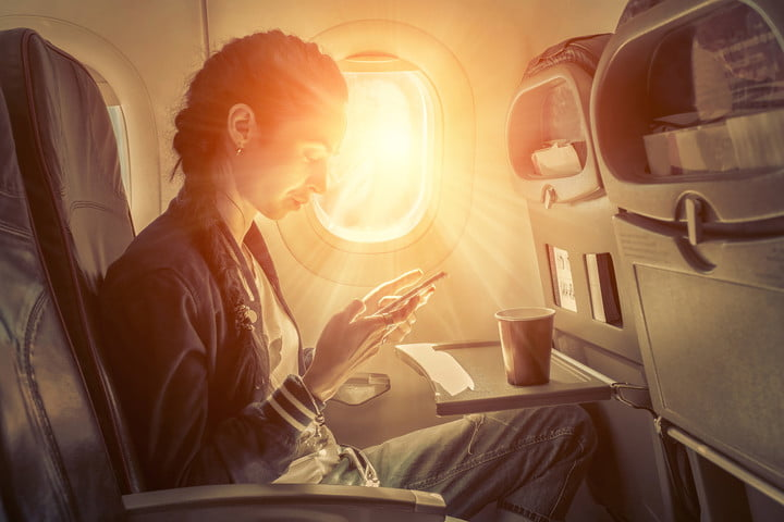 alaska airlines solar eclipse woman typing on phone in airplane sunlight
