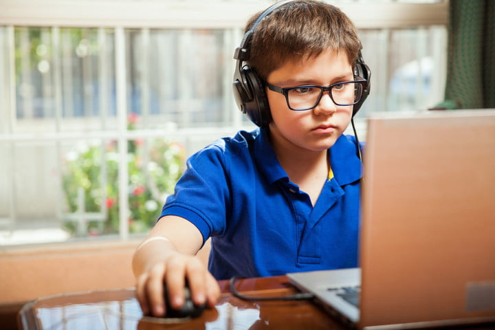 digital divide smartphones dont help young boy working on computer with headphones and mouse